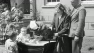 1950 MONTAGE Foster parents arriving at orphanage and picking up their new infant foster daughter / United Kingdom