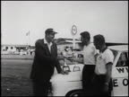 WS NASCAR founder Bill France Sr handing a check and then shaking hands with one of two members of the AMC Rambler team that won the 1960 Pure Oil...
