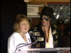 Founder of the Michael Jackson Observer Fan Club Lori Byler speaking at podium outside Guinness Museum presenting award Michael Jackson standing next...
