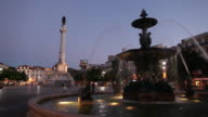 WS Fountain and Column of Pedro IV on Rossio Square at dusk / Lisbon, Portugal
