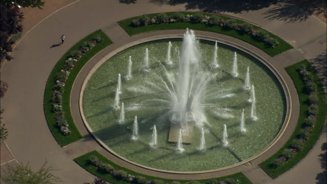 AERIAL MS ZO WS ZI Fountain in park with surrounding traffic circle and cityscape / Dijon, France