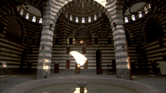 A fountain stands open to the sky below an open semi-dome in the Khan Asad Pasha Damascus. Available in HD.