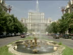 Fountains gush water as traffic drives along Unirii Boulevard Ceaucescu's Palace world's second biggest building stands in distance Bucharest