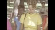 / four African American women walk through Central Park