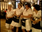 Four American diner waitresses stand in a row in restaurant gossiping and looking around
