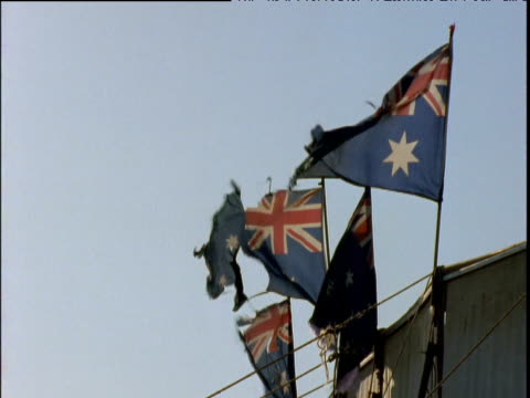 Four Australian flags flapping in breeze moth eaten and ragged