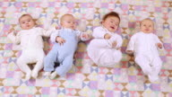 MS Four babies (6-11 months) lying on fabric / Brussels, Belgium