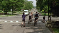 WS TS PAN Four boys riding bikes and skateboarding down road, three turn corner and one continues straight on road / Cazenovia, New York, USA