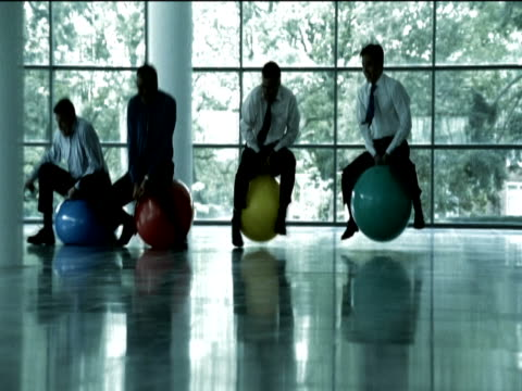 Four Businessmen Race on Multi-Coloured Space Hoppers on the Floor of an Office Building