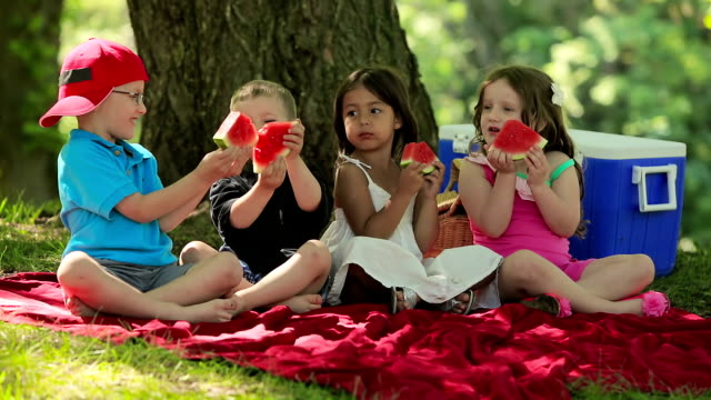 Four children have fun eating fruit together