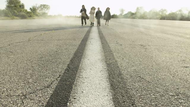 Four children on a runway, walking towards camera