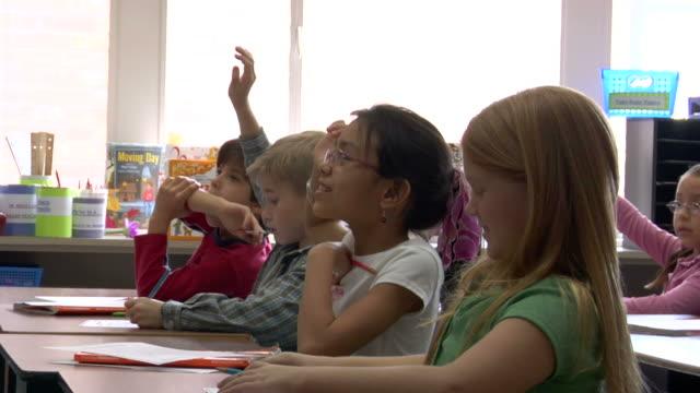 CU, Four children (6-7, 8-9) raising hands in classroom