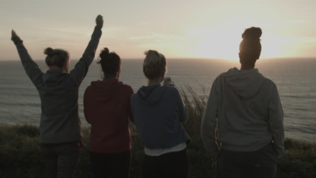 Four friends looking at sunset at ocean taking photos with cell phones