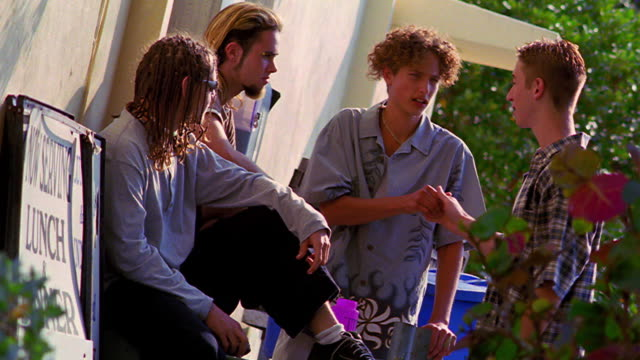 CANTED four Generation X teen boys shaking hands + greeting each other outdoors