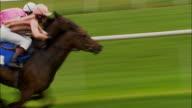 TS WS ZI ZO Four jockeys on horses running during race at Newbury Racecourse / Newbury, England, UK
