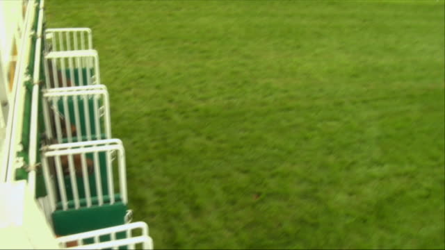 SM OH WS Four jockeys on horses running out of starting gates during race at Newbury Racecourse / Newbury, England, UK