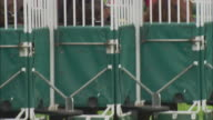 CU TU MS PAN ZI Four jockeys sitting on horses inside gates before race at Newbury Racecourse / Newbury, England, UK