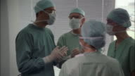 Four medical professionals in surgical gowns and masks stand in a circle talking.