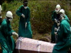 Four men in protective clothing lower coffin of Ebola virus victim into ground Africa