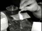 Four men working at kitchen table diluting cutting heroin weighing for packaging CU Weighing spoonfull herion on scale