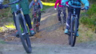Four mountain bikers going down the forest trail and through a puddle
