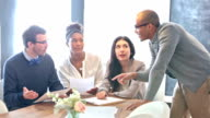 Four multi-ethnic young adults having a business meeting
