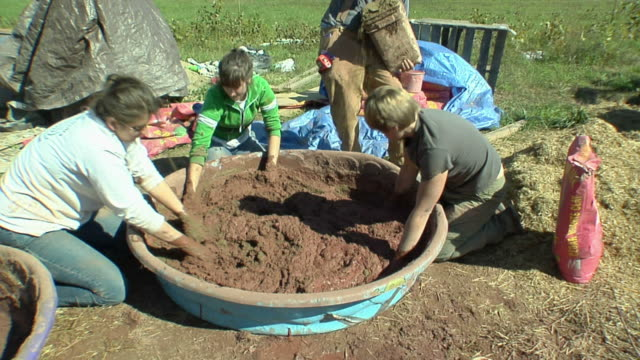 MS Four people mixing up adobe mud used to coat walls of straw house, Grass Lake, Michigan, USA