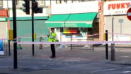 Four police officers stabbed in North London General views of crime scene ENGLAND North London Kingsbury EXT Police officer outside butchers shop /...
