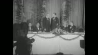 Four shots of Marshall on left standing with Secretary of Defense at banquet table talking and posing for photo opportunity other men sitting at...