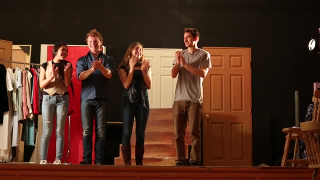 Four teenage actors bowing at the conclusion of a theater performance