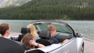 Four teens drive convertible to mountain lake, leave and view scene