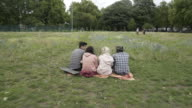 Four teens sitting together in a huddle on the grass.