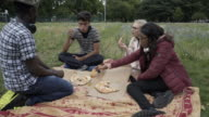Four teens together eating pizza in the park.