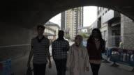 Four teens walking along a street.