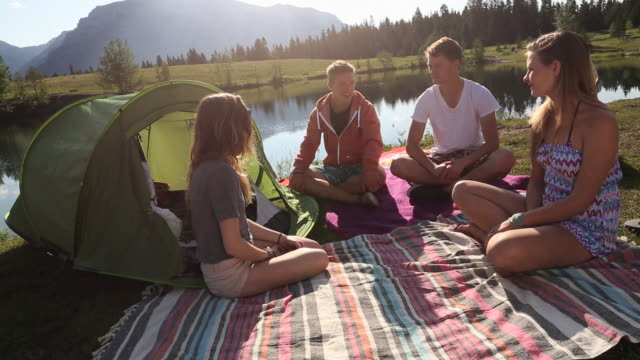 Four teens with tent & blankets use digital tablet, mtn lake