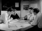 Four unidentified architects engineers working on plans at table TD WS Scale model of new business complex AJAX ARIAL WS Small lot housing...