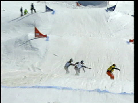 Four women on snowboards race round course during competition Switzerland