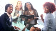 Four young business people in meeting, woman in charge