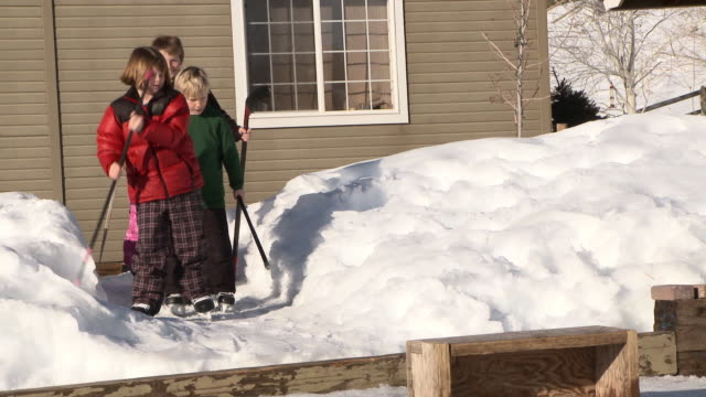 Four young kids bring hockey sticks out to backyard ice rink / Bellevue, Idaho, United States
