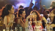 Four young women drinking tequila at nightclub party