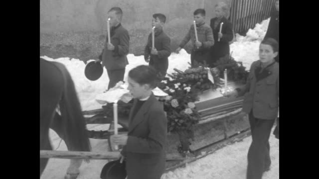 Fourteen coffins laid on snow / VS procession with coffins on sleighs pulled by horses with children and women in traditional costumes walking...
