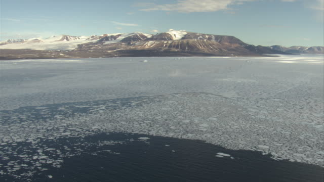 Fragmenting sea ice floats past the mountainous coast of North Baffin Island.