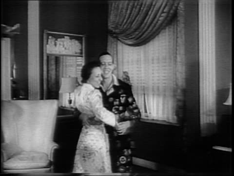 Frank L Lillyman and wife dancing in hotel suite with daughter and maid in foreground / close up of record player / Lillyman and wife dancing /...