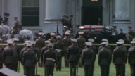 Franklin D Roosevelt's funeral procession at the front of the White House soldiers at attention and casket being removed from caisson and carried...