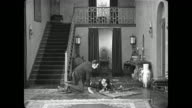 Frantic Buster Keaton runs through crowded room before colliding with man in hallway and hitting himself in the head with the door