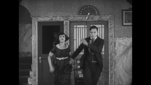 Frantic Buster Keaton escapes hotel with girlfriend before entering home furnishings shop carrying woman over his shoulder