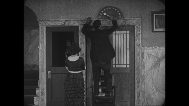 Frantic Buster Keaton tricks pursuer into empty elevator shaft before hiding again, meeting his girlfriend and escaping hotel
