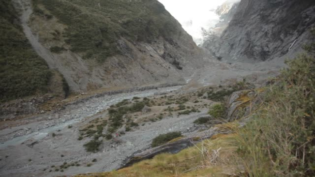 Franz Josef Glacier in Westland Tai Poutini National Park with some high cloud cover and rocky bed of Waiho River