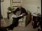 Bishop of Gloucester seated reading newspaper