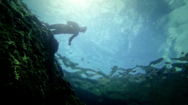 Free diver descending in the abyss